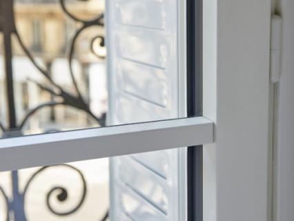Zoom petit bois intérieur en applique sur le vitrage d'une fenêtre en bois